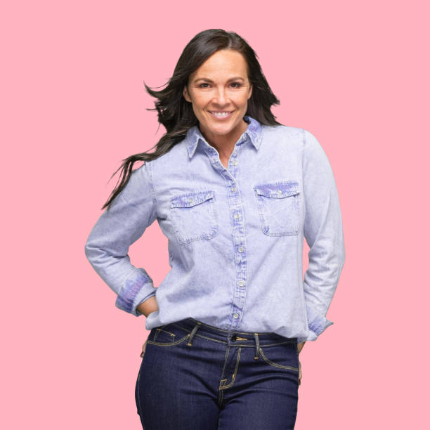 Caucasian young women cowgirl in front of colored background wearing shirt stock photo