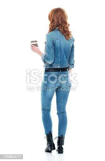 Full length of aged 20-29 years old who is beautiful with redhead caucasian young women standing in front of white background wearing jeans and holding coffee cup