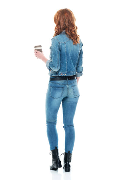 Caucasian young women standing in front of white background wearing jeans and holding coffee cup stock photo