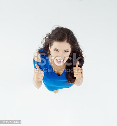 One person of aged 20-29 years old who is beautiful with long hair caucasian young women standing in front of white background wearing dress who is cheerful and showing ok sign