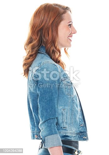Profile view of aged 20-29 years old who is beautiful with long hair caucasian young women standing wearing jacket who is smiling with hand by side