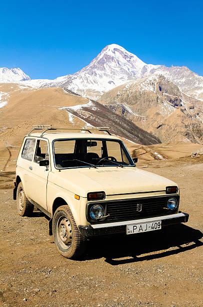 kaukasus im frühling mit schnee und lada niva jeep - lada niva stock-fotos und bilder