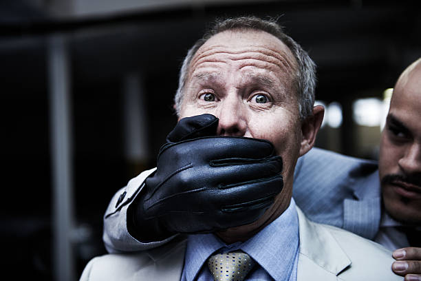 Caught unawares Portrait of a shocked businessman caught unawares by an assailant in the parkade ambush stock pictures, royalty-free photos & images