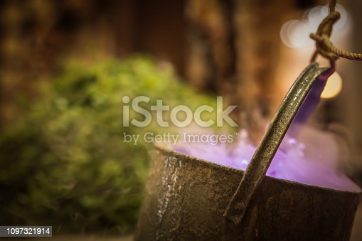 Cauldron with purple magic boiling potion or witching toxic poison soup. Object for Halloween, horror or fantastic themes