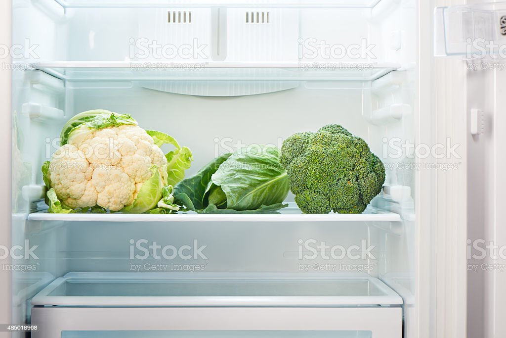 Cauliflower, green cabbage and green broccoli on shelf of refrigerator stock photo