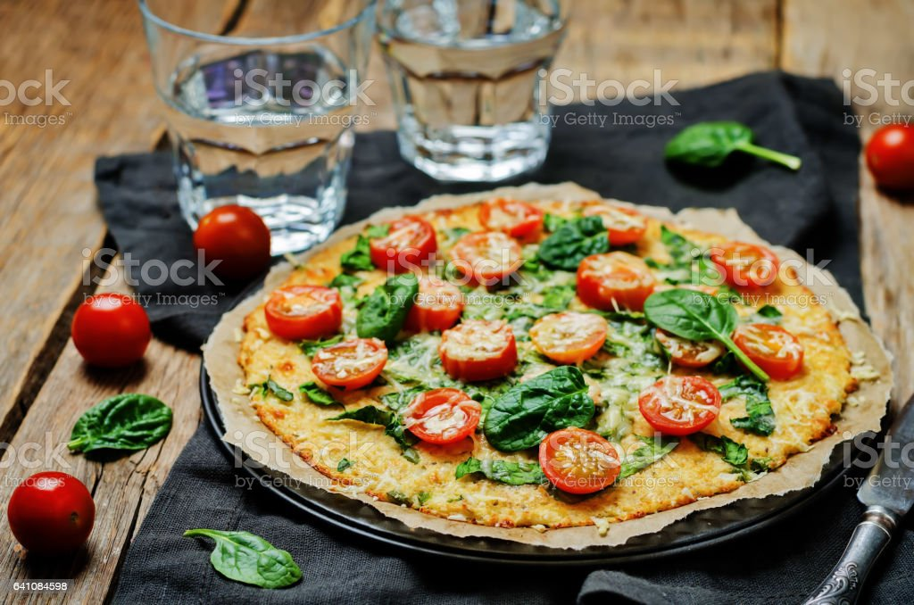 Cauliflower pizza crust with tomato and spinach stock photo