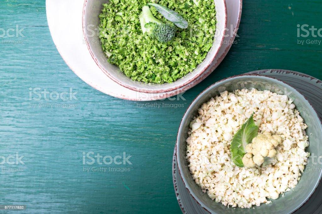 Arroz de coliflor y brócoli en tazón de fuente sobre fondo verde. Vista superior. Arriba. Copia espacio. Rallado. - foto de stock