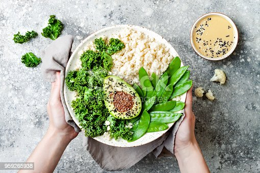 Cauliflower rice Buddha bowl with kale, avocado, seeds, snow peas and tahini dressing