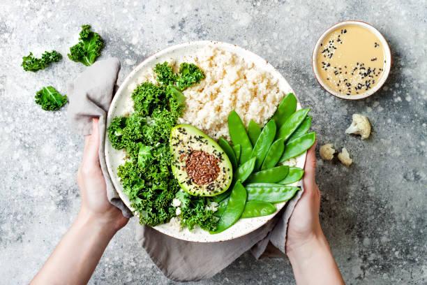 Cauliflower rice Buddha bowl with kale, avocado, seeds, snow peas stock photo