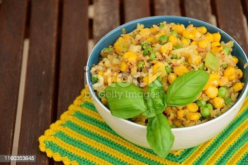 Cauliflower rice with corn and peas garnish with basil leaf