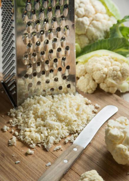 blumenkohl-reis mit reibe und leiter der blumenkohl auf chopping board mit messer - gebackener blumenkohl stock-fotos und bilder