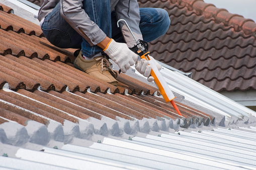 Technician man hand using glue gun with silicone adhesive or manual caulking gun with polyurethane to seal the leak on the roof. Installing and building construction concept.