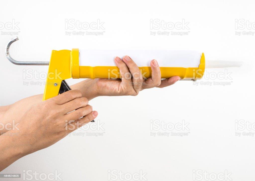 Caulking Gun in Hand stock photo