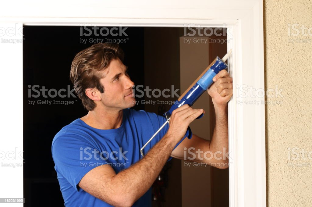 Caulking Gun Man in Blue Shirt stock photo