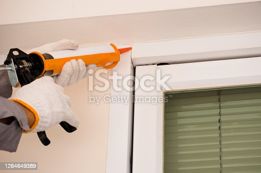 Technician man hand holding and using manual caulking glue gun or silicone tube to seal the expansion joint between cement wall and steel material at aluminium door. Construction maintenance concept.