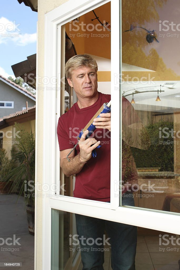 Caulking Man Insulates Window stock photo