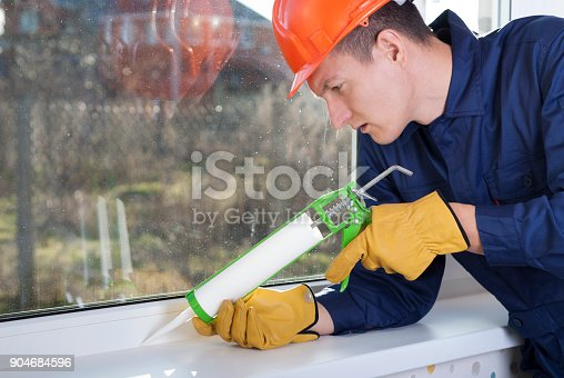 istock caulking window frame with silicone sealant 904684596