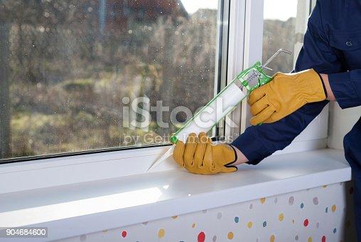istock caulking window frame with silicone sealant 904684600