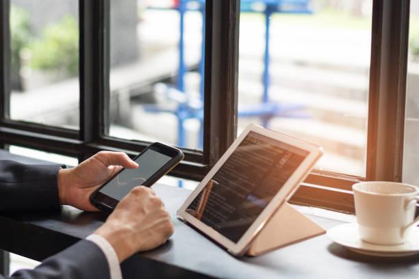 causal professionelle business-mann mit multichannel-dienste mit internet-wlan 5g auf smartphone und online-tablet im café. city lifestyle geschäftsmann hände arbeiten mit handy-konzept - www kaffee oder tee stock-fotos und bilder