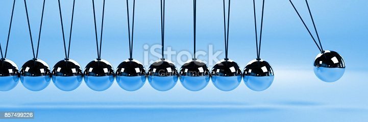istock cause and effect concept banner, metal Newton's cradle on a blue background, 3D illustration 857499226