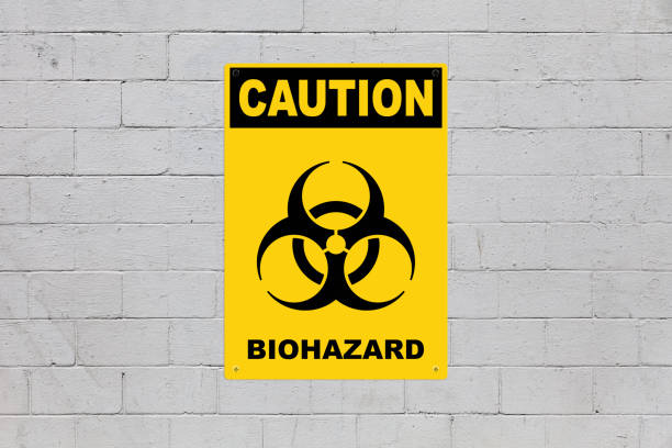 Caution - Biohazard Yellow warning sign screwed to a brick wall to warn about a threat. In the middle of the panel, there is a biohazard symbol and the message is saying