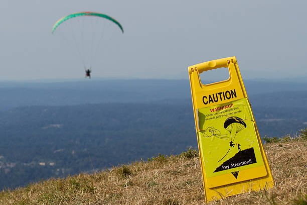 Caution Sign with paraglider on background stock photo