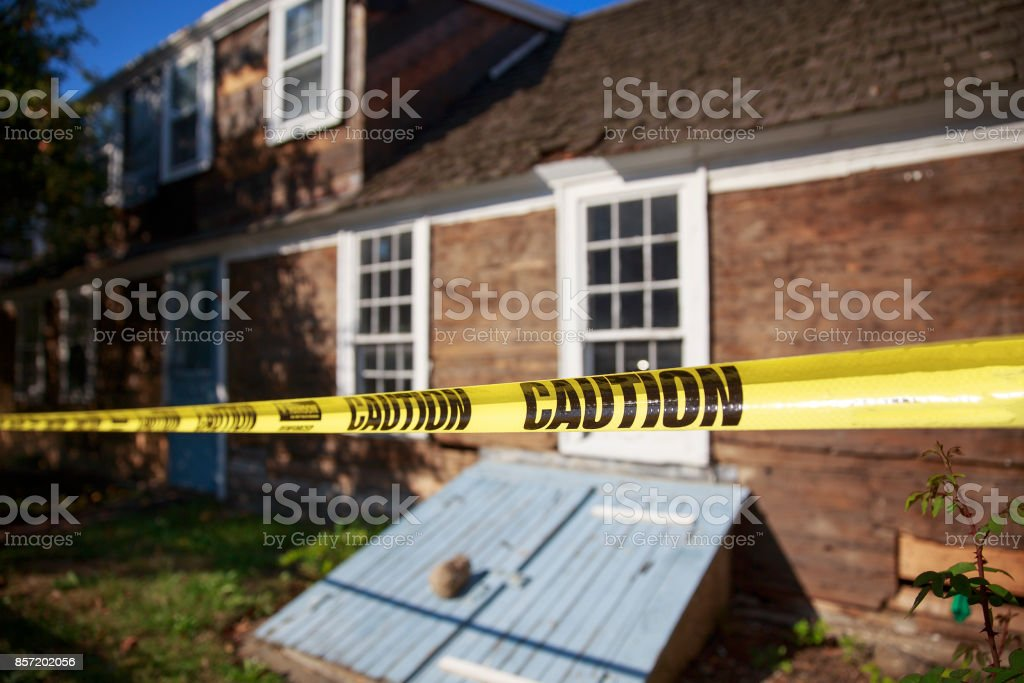caution tape blocking the way into the building stock photo