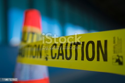 Yellow caution tape attached to traffic cone