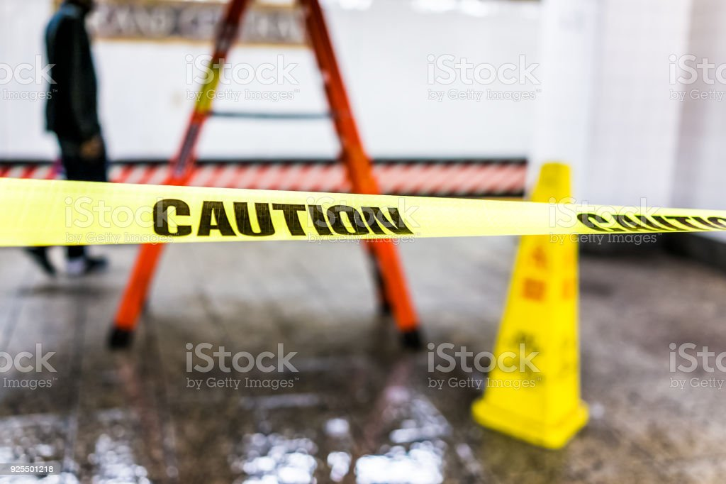 Caution tape sign in underground transit empty large platform in New York City NYC Subway Station in Grand Central, ladder, wet floor cone stock photo