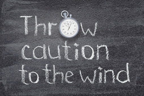 Throw caution to the wind - English proverb  written on chalkboard with vintage precise stopwatch