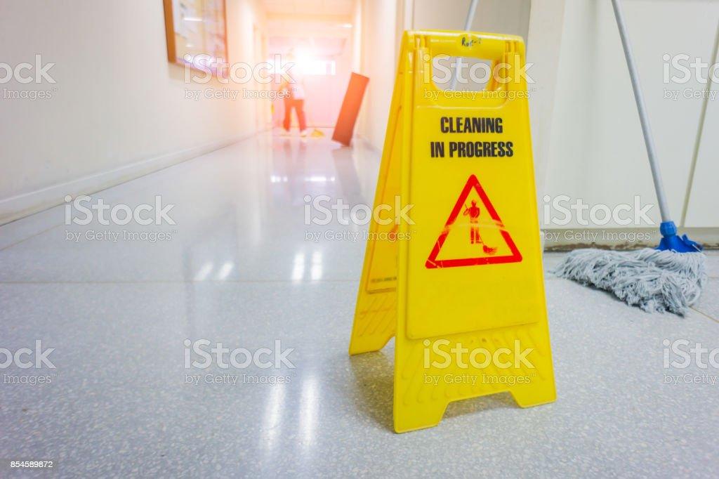 Vorsicht nassen Boden Warnschild mit unscharfen Arbeiter, Boden wischen – Foto