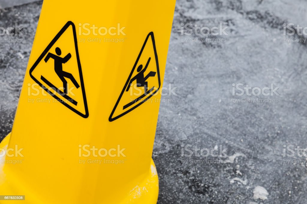 Caution wet floor, yellow warning sign on asphalt stock photo