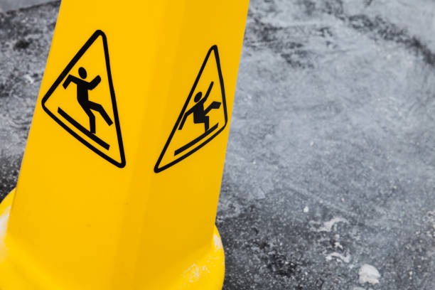 caution wet floor, yellow warning sign on asphalt - fall prevention stock photos and pictures