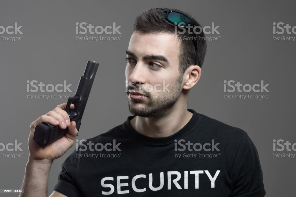 Cautious alerted security guard holding gun looking back over shoulder. stock photo