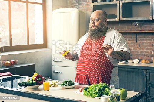 istock Cautious fat man preparing vegetable salad 680412674