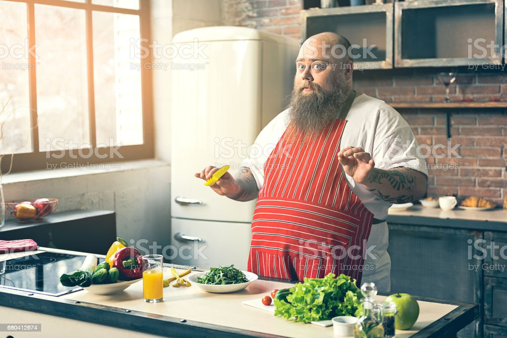 Cautious fat man preparing vegetable salad stock photo