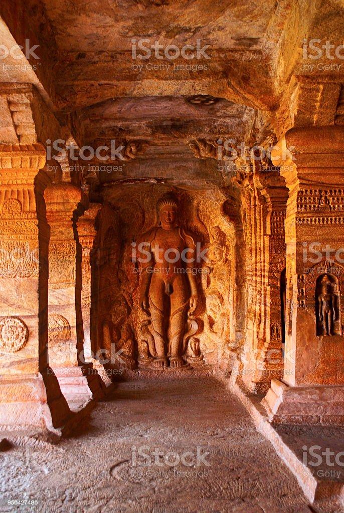 Höhle 4: Geschnitzte Figur von Bahubali mit seinen Unterschenkel umgeben von Schlangen, zusammen mit seinen Töchtern Brahmi und Sundari. – Foto