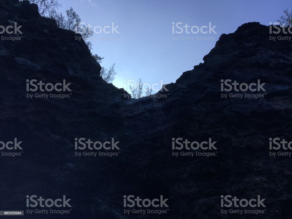 Cave and Waterfall in Mountains and Cliffs on Napali Coast on Kauai Island in Hawaii - View from Pacific Ocean. stock photo
