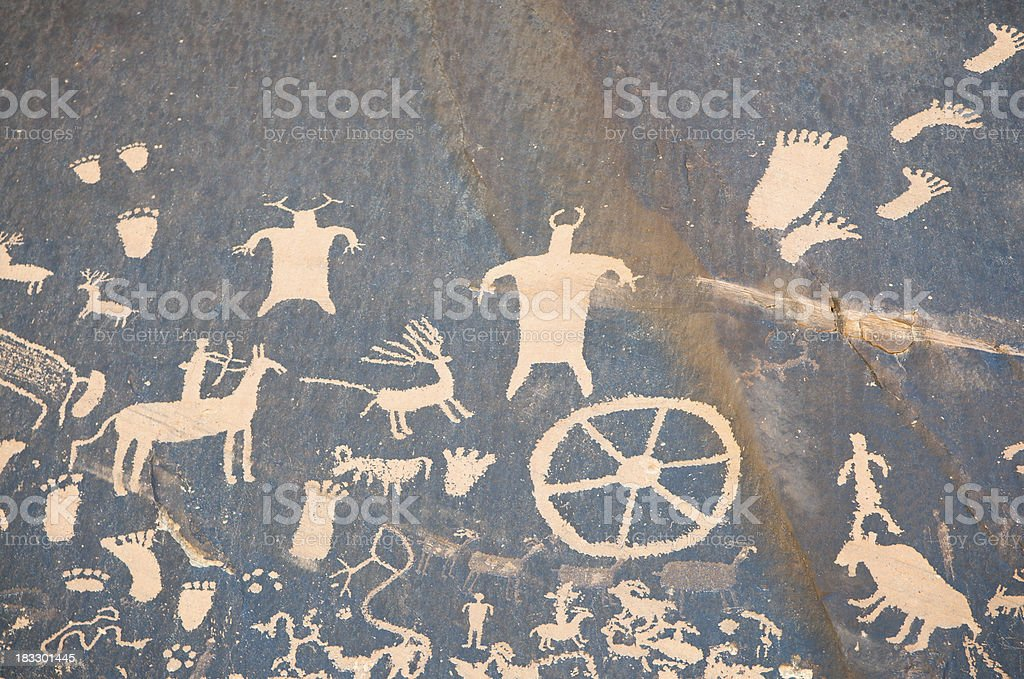 Cave Drawing with Hunters and Wheels stock photo