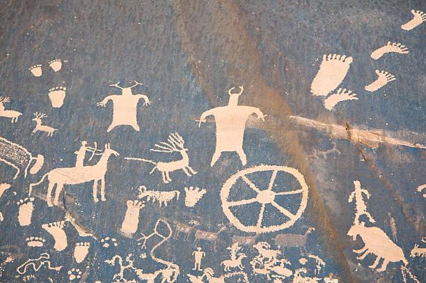 cave drawing with hunters and wheels - mağara resmi stok fotoğraflar ve resimler