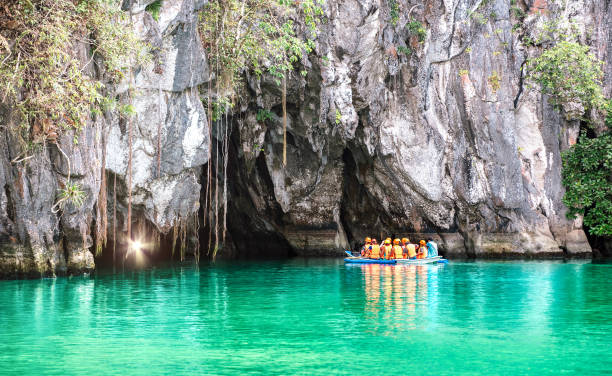 Cave entrance of Puerto Princesa subterranean underground river with longtail boat - Wanderlust travel concept at Palawan exclusive Philippine destination - Vivid filter with bulb torch light sunflare stock photo