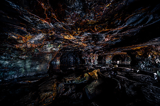 Dark cave with a human skeleton leaning against wall\n\nThe caves a public caves at Västra Tunhem in Sweden. No entry fees and property release necessery. The skeleton is my own