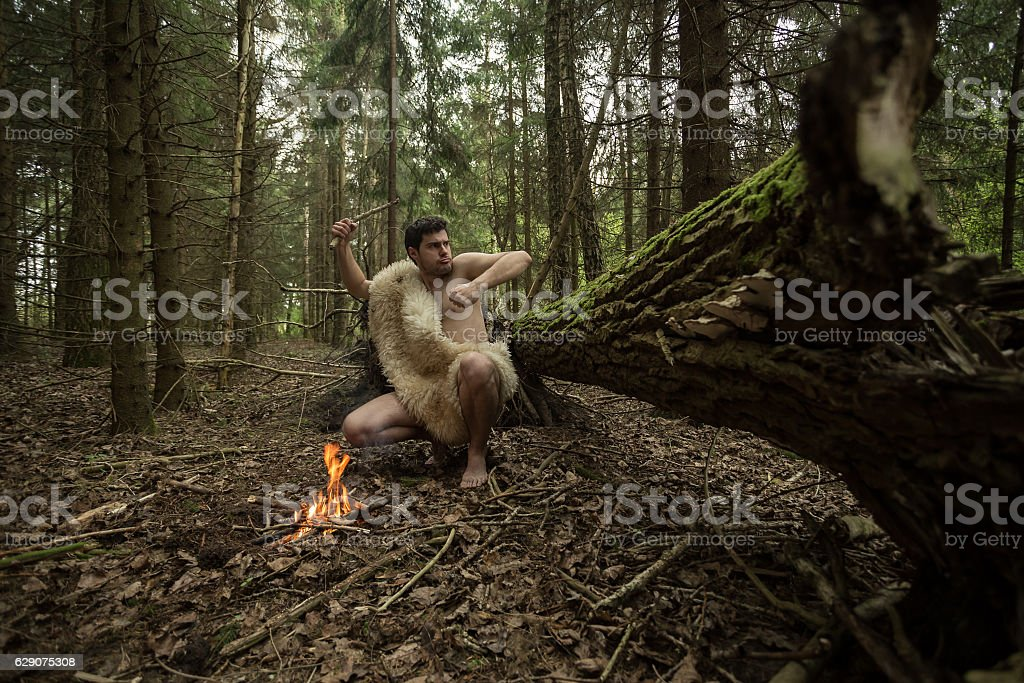 Caveman in animal skin kindles a fire in the forest stock photo