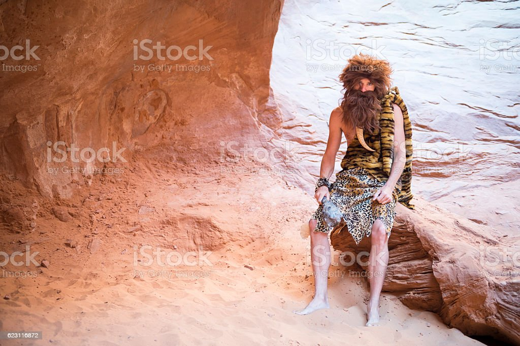 Caveman Sitting in Cave stock photo