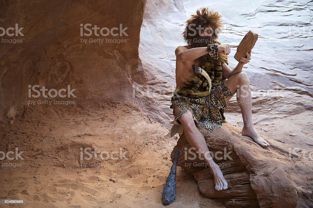 Caveman Sitting Outdoors Using Stone Tablet with Touchscreen Caveman sitting using touchscreen stone tablet outdoors in a weathered rock cave Adult Stock Photo
