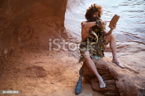 Caveman sitting using touchscreen stone tablet outdoors in a weathered rock cave