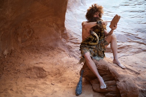 Caveman Sitting Outdoors Using Stone Tablet With Touchscreen Stock Photo - Download Image Now
