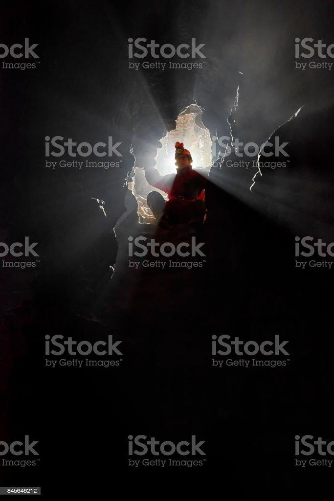 Caver exploring a narrow passage stock photo