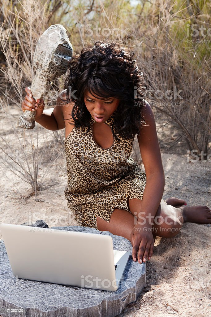 Cavewoman about to hit laptop with club stock photo