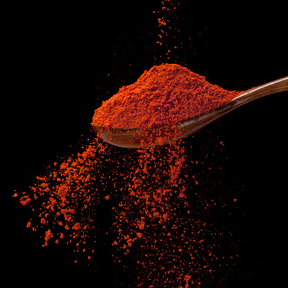 Cayenne pepper is flowing-photographed  on black background